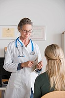 Female doctor talking to patient in her office