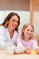 Portrait of a beautiful mother and her daughter having breakfast in a kitchen
