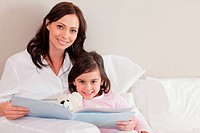 Happy mother reading a story to her daughter in a bedroom