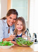 Portrait of a mother and her daughter preparing a salad in their kitchen
