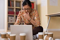 Woman working on laptop surrounded by empty coffee cups