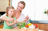 Mother and daughter stirring salad together
