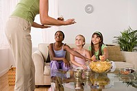 Woman serving food for three girls 10_11 at slumber party