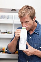 Man smelling milk jug for freshness