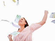 Woman under bank notes falling against a white background