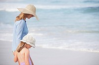 Mother and daughter in sun hats walking on beach