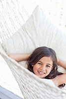 Portrait of smiling girl laying in hammock with hands behind head