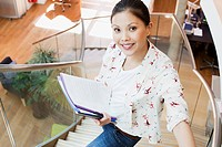 Portrait of smiling businesswoman holding paperwork on stairs