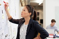 Businesswoman looking at information on whiteboard in office