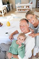 Portrait of smiling parents with daughter at breakfast table
