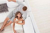 Smiling woman laying on man's lap on sofa (thumbnail)