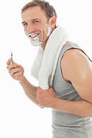 Portrait of smiling man shaving face with razor