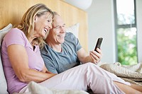 Senior couple looking at cell phone in bed