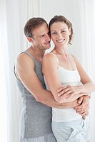Portrait of smiling couple hugging in pajamas