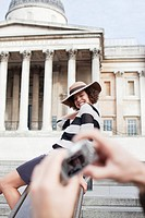 Man taking photograph of woman posing in front of London building