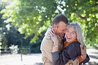 Portrait of smiling couple hugging in sunny park