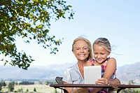 Grandmother and granddaughter using digital tablet at table outdoors