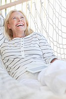 Happy senior woman laying in hammock with digital tablet