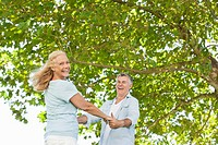 Portrait of happy senior couple holding hands under tree