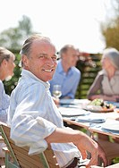 Portrait of smiling man enjoying lunch at patio table with friends