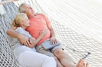 Serene senior couple laying in hammock with eyes closed