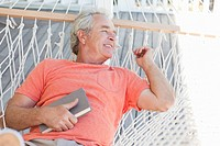 Senior man laying in hammock with book