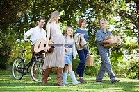 Multi_generation family with bicycle, apples and guitar in orchard