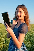 Teen girl with electronic book reader outdoors