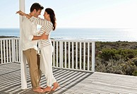 Smiling couple hugging face to face on patio overlooking ocean (thumbnail)