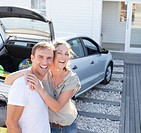 Portrait of smiling couple hugging in driveway (thumbnail)