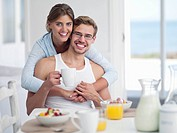 Portrait of smiling couple enjoying breakfast at table (thumbnail)