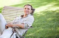 Portrait of confident man sitting on park bench