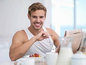 Portrait of smiling man reading newspaper at breakfast table
