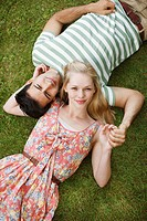 Portrait of smiling couple laying in grass and holding hands