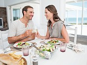 Smiling couple eating lunch and toasting wine glasses at table