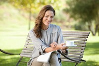 Portrait of smiling woman drinking coffee and reading magazine on park bench