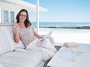 Portrait of smiling woman with paperwork on patio overlooking ocean
