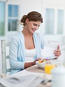 Smiling woman reading letter at breakfast table