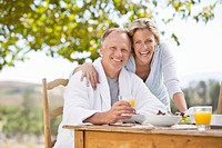 Portrait of smiling couple enjoying breakfast at garden table
