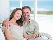 Portrait of smiling couple hugging on patio overlooking ocean