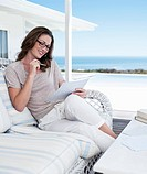 Smiling woman looking at paperwork on patio overlooking ocean