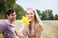 Portrait of couple with yellow pinwheel in sunny rural field