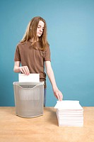 Teen Boy in Act of Shredding Blank Paper