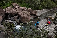 Couple crossing creek with bicycles