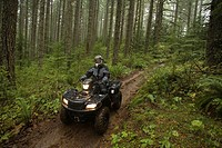 Man Riding ATV through Forest