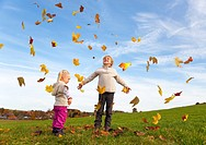 Children playing in fall leaves