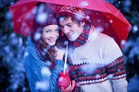 Smiling couple under umbrella in snow