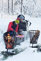 Couple picnicking by fire in snow