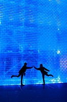 SIlhouettes of two young girls in ballet poses against a blue light glass brick wall at Crown Fountain in Millennium Park in Chicago Illinois USA