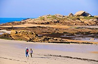 2 persons walking on beach, spectacular rocks along Pink Granite Coast, Ploumanach, Côtes-d'Armor, Brittany, France